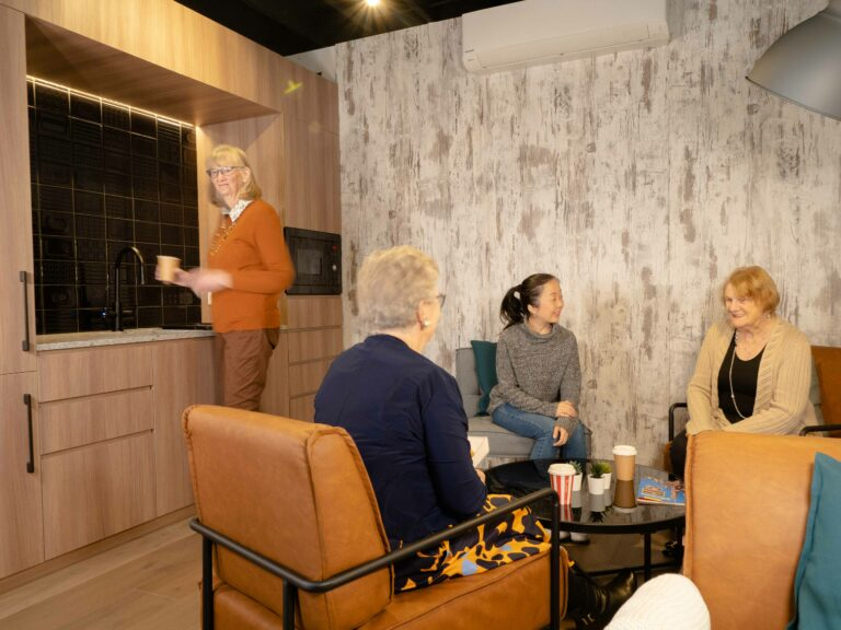 Community meet on couches and kitchenette in Little BIG House